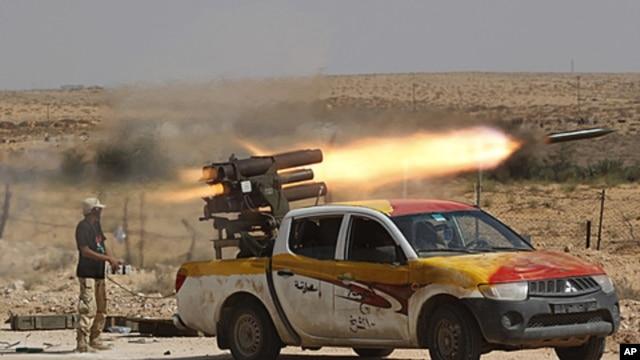 An anti-Gaddafi fighter fires a multiple-rocket launcher near Sirte, the hometown of deposed leader Moammar Gaddafi, September 17, 2011.