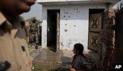 FILE - Indian security personnel inspect a house allegedly damaged by from gunfire from the Pakistan side of the border, at a residential area near the international border at Bidipur, in Ranbir Singh Pura, India, Oct. 22, 2016.