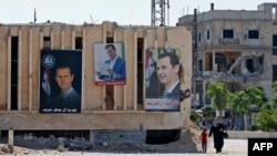 Портреты Башара Асада на здании избирательного участка в городе Дума, недалеко от Дамаска, 26 мая 2021 года