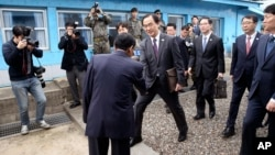 South Korean Unification Minister Cho Myoung-gyon, center, shakes hands with a North Korean official as he crosses to North Korea for the meeting at the northern side of the Panmunjom in North Korea, Thursday, March 29, 2018. (Korea Pool via AP)