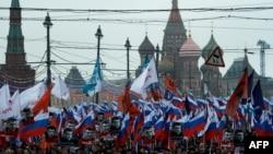 ကရင္မလင္နန္းေတာ္နားက တံတားေပၚမွာ ေသနတ္နဲ႔လုပ္ႀကံခံရသူ အတုိက္အခံေခါင္းေဆာင္ Boris Nemtsov ကို ေထာက္ခံသူေတြက ႏုိင္ငံေတာ္အလံေတြကိုင္ၿပီး ခ်ီတက္ဂါရဝျပဳေနစဥ္။ (မတ္ ၁၊ ၂၀၁၅)