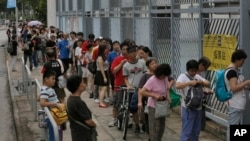 People line up at a polling center to vote in an unofficial referendum on democratic reform in Hong Kong, June 22, 2014.
