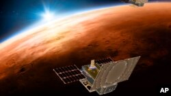 Esta ilustración distribuida por NASA el 29 de marzo de 2018 muestra los satélites gemelos Mars Cube One sobrevolando Marte, con el sol y la Tierra en el fondo. (NASA/JPL-Caltech via AP)