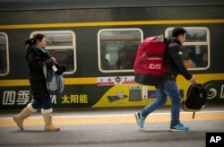 Passengers run to board a train at the Beijing Railway Station in Beijing, Jan. 30, 2016.