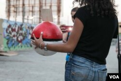 A Pokemon GO fan poses with a replica Pokeball during a gathering organised and backed by a Lebanese tech firm, which hid energy drinks in the Pokeballs.