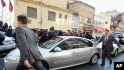 Security members and journalists surround a car with Turkey's former Chief of Staff Gen. Ilker Basbug inside as he arrives at a prosecutor's office in Istanbul, January 5, 2012.