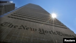 FILE PHOTO: The sun peaks over the New York Times Building in New York on Aug. 14, 2013.