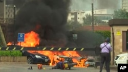 Beberapa ledakan terdengar sementara mobil-mobil terbakar di sekitar lokasi serangan di Nairobi, Selasa (15/1).