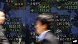 Hombres de negocios caminan frente a la pizarra electrónica de una firma de inversiones, en Tokio. El Fondo Monetario Internacional ha reducido las perspectivas globales de crecimiento.