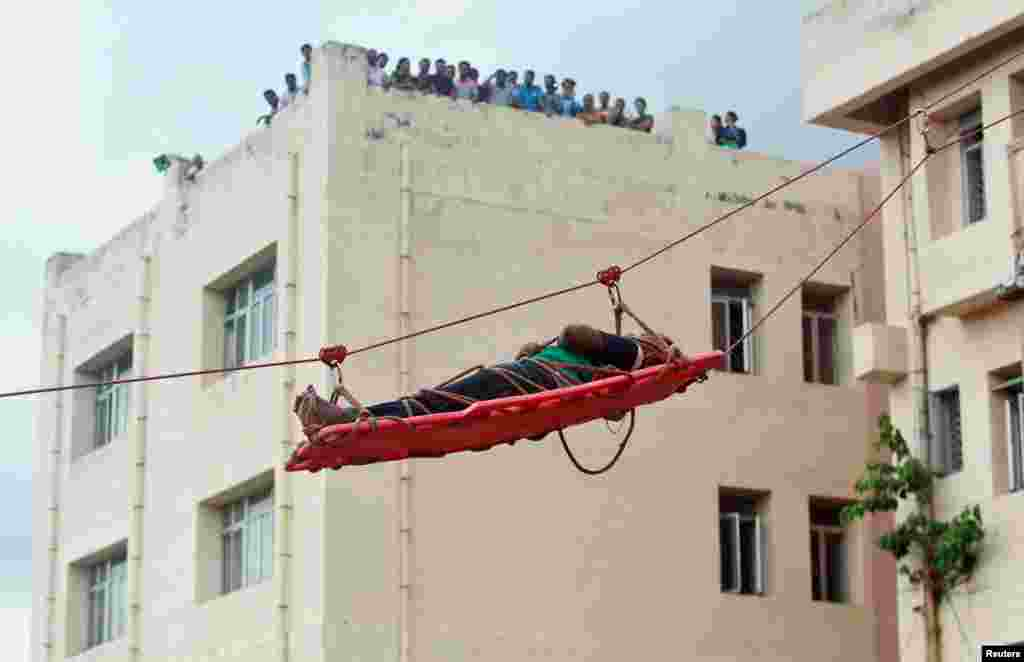 A simulated victim is lowered on a stretcher during an earthquake drill in Agartala, India.