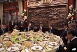 """中国国家主席习近平,俄罗斯总统普京和外交部长拉夫罗夫(习近平右侧)在北京的 """"一带一路""""国际合作高峰论坛开幕式前的早餐会上交谈(2017年5月14日)。"""