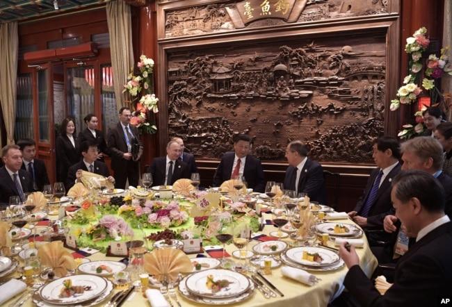 """中國國家主席習近平,俄羅斯總統普京和外交部長拉夫羅夫(習近平右側)在北京的""""一帶一路""""國際合作高峰論壇開幕式前的早餐會上交談(2017年5月14日)。"""