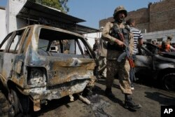 A Pakistani soldier walks past damaged vehicles at the site of a deadly suicide bombing in Charsadda, Pakistan, Monday, March 7, 2016.