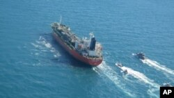In this photo released Monday, Jan. 4, 2021, by Tasnim News Agency, a seized South Korean-flagged tanker is escorted by Iranian Revolutionary Guard boats on the Persian Gulf. (Tasnim News Agency via AP)
