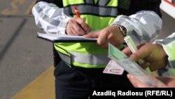 Arxiv fotosu - Yol polisi sürücünü cərimələyir