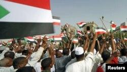 Mutane su na daga tutar Sudan ma sojoji a lokacin wani maci na murnar nasarar da suka samu a kofar ma'aikatar tsaro dake Khartoum ranar 20 Afrilu, 2012.