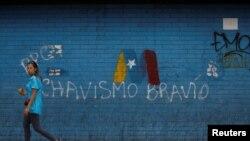 Una mujer pasa frente a un graffiti de la campaña de Nicolás Maduro para las elecciones presidenciales en Venezuela el 8 de mayo de 2018. Foto: Reuters/Adriana Loureiro.