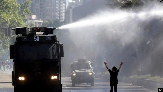 Un blindado policial dispara un cañón de agua a los manifestantes durante las protestas en Chile el 21 de octubre de 2019. AP.
