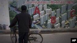 Một người đàn ông dừng xe đạp để xem hình vẽ của một dự án bất động sản bên ngoài công trường xây dựng ở Bắc Kinh, ngày 17/1/2013.