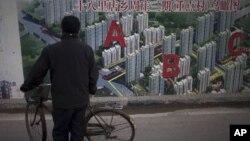 Seorang warga tengah mengamati gambar peta proyek perumahan yang dipajang di pembatas wilayah sebuah konstruksi di Beijing, TIongkok, 17 Januari 2013. (AP Photo/Alexander F. Yuan). Laju pertumbuhan ekonomi Tiongkok dilaporkan meningkat menjadi 7,9 persen pada kuartal ke-4 tahun 2012 yang lalu.
