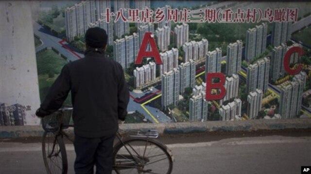 Một người đàn ông dừng xe đạp lại để ngắm một bức hình dự án một khu dân cư bên ngoài địa điểm xây dựng trong thủ đô Bắc Kinh của Trung Quốc.
