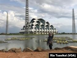 Seorang wanita berfoto di Embung Gedebage, Kota Bandung, yang berdampingan dengan Masjid Raya Jawa Barat. Bersama dua proyek lainnya, embung ini dibuat untuk kendalilan air di Bandung Raya.