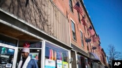 U.S. flags hang outside a downtown building whose storefronts are made up of businesses started by African immigrants who have settled in Lewiston, Maine, March 17, 2017. Maine's immigrants from Sub-Saharan Africa made $136.6 million in income in 2014, and paid $40 million in taxes, according to a report from the New American Economy.
