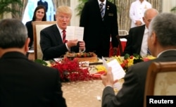 President Trump holds up the menu as he attends a lunch with Singapore's Prime Minister Lee Hsien Loong at the Istana in Singapore, June 11, 2018. (Ministry of Communications and Information, Singapore/Handout via Reuters)