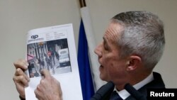Paris prosecutor Francois Molins shows a photograph of the suspect gunman taken from surveillance footage during a news conference in Paris, Nov. 18, 2013.