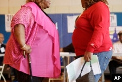 FILE: In this June 26, 2012, photo, two overweight women hold a conversation in New York.