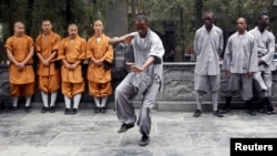FILE - An African student practices moves as other Shaolin martial arts students look on during the inauguration ceremony of a martial arts training program for African students, at the Shaolin Temple in Dengfeng, Henan province, Sept. 2013.