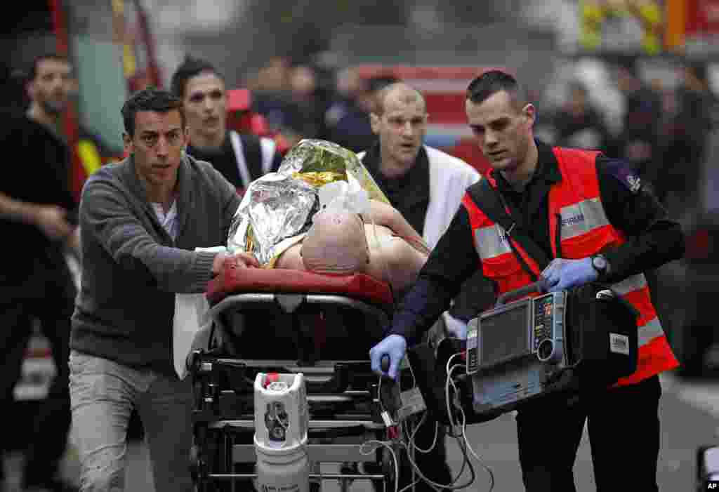 An injured person is given medical care outside the offices of Charlie Hebdo, in Paris, Jan. 7, 2015.