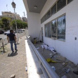 A man checks the damaged US embassy after pro-government protesters attacked the embassy compound in Damascus, Syria, July 11, 2011