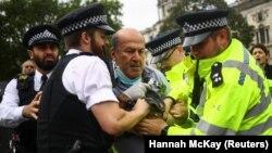 Policija odvodi demonstranta za koga se smatra da je istrčao pred vozilo u kome se nalazio britanski premijer