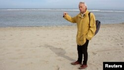 FILE - Jasper Fiselier, an environmental planning expert at Dutch engineering consultants Royal HaskoningDHV, stands on a beach at Ter Heijde, the Netherlands.