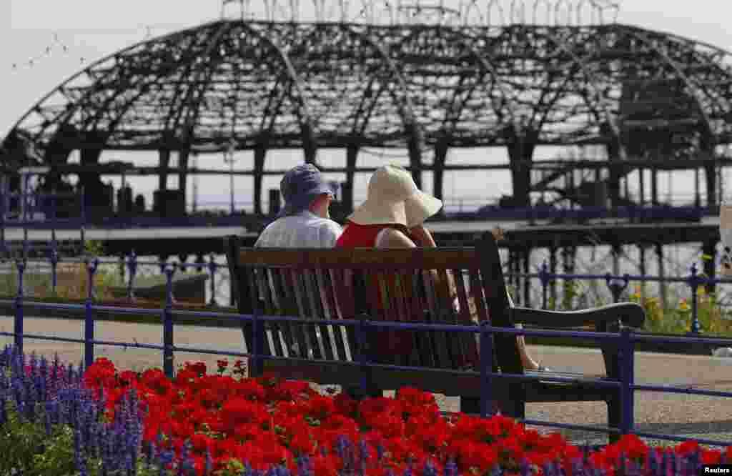 7月31日,一对夫妇坐在广场上看英格兰东部的斯特本港口某一段被火烧后的残骸。
