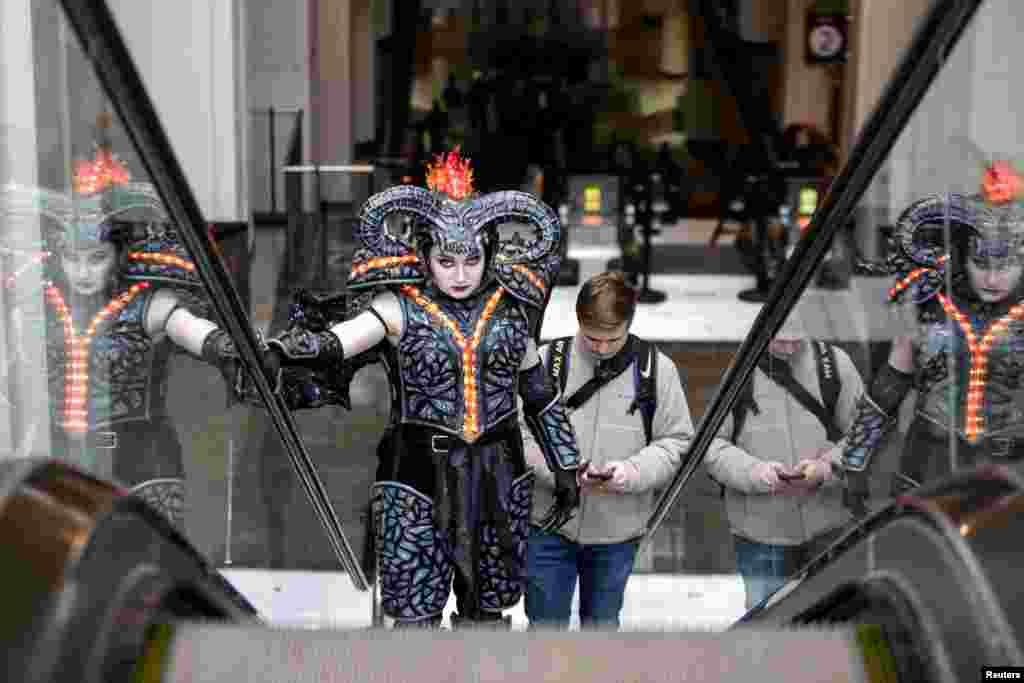 "Emma Randall, dressed as Balrog from ""The Lord of the Rings,"" and boyfriend Connor Sauby, ascend an escalator as a small group of cosplayers gather at the Washington State Convention Center in Seattle, Washington, for what would have been the 2020 Emerald City Comic Con. The event will be postponed to August due to the coronavirus (COVID-19) outbreak."