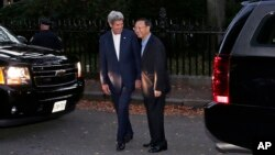 Secretary of State John Kerry, left, walks with Chinese State Councilor Yang Jiechi outside Kerry's home on Beacon Hill in Boston, Friday, Oct. 17, 2014.