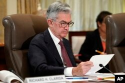 FILE - Federal Reserve Chair Jerome Powell looks over papers during a meeting at the Fed's offices in Washington, Oct. 31, 2018.