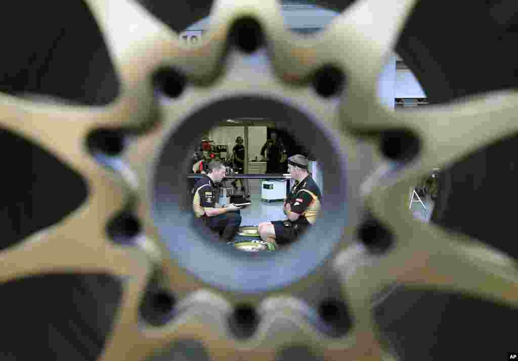 Lotus mechanics, seen through a wheel, talk to one another at the garage of the Marina Bay City Circuit in Singapore. The Formula One Singapore Grand Prix will be held on Sept. 22 in the city-state.