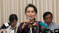 Myanmar opposition leader Aung San Suu Kyi, center, talks to journalists during a news conference at her residence, Saturday, July 11, 2015.
