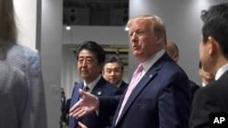 參加大阪20國集團峰會的美國總統特朗普和日本首相安倍晉三走在一起。(2019年6月28日)