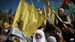 Les Palestiniens brandissent le drapeau national et celui du mouvement Fatah lors d'un rassemblement marquant le 13ème anniversaire de la mort du fondateur du Fatah et dirigeant de l'Autorité palestinienne Yasser Arafat, dans la ville de Gaza,11 novembre 2017.