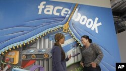 Two workers talk inside Facebook headquarters in Menlo Park, California, February 8, 2012.
