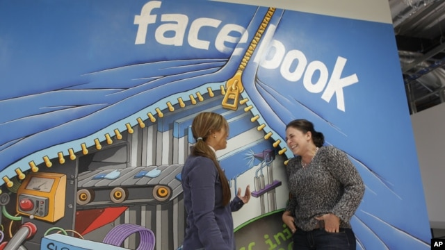 Two workers inside of Facebook headquarters in Menlo Park, Calif