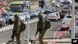 Israeli soldiers stand at the scene of an attack near the settlement of Givat Assaf in the West Bank, Dec. 13, 2018. A Palestinian gunman opened fire at a bus stop outside a West Bank settlement Thursday, killing at least two Israelis before fleeing.
