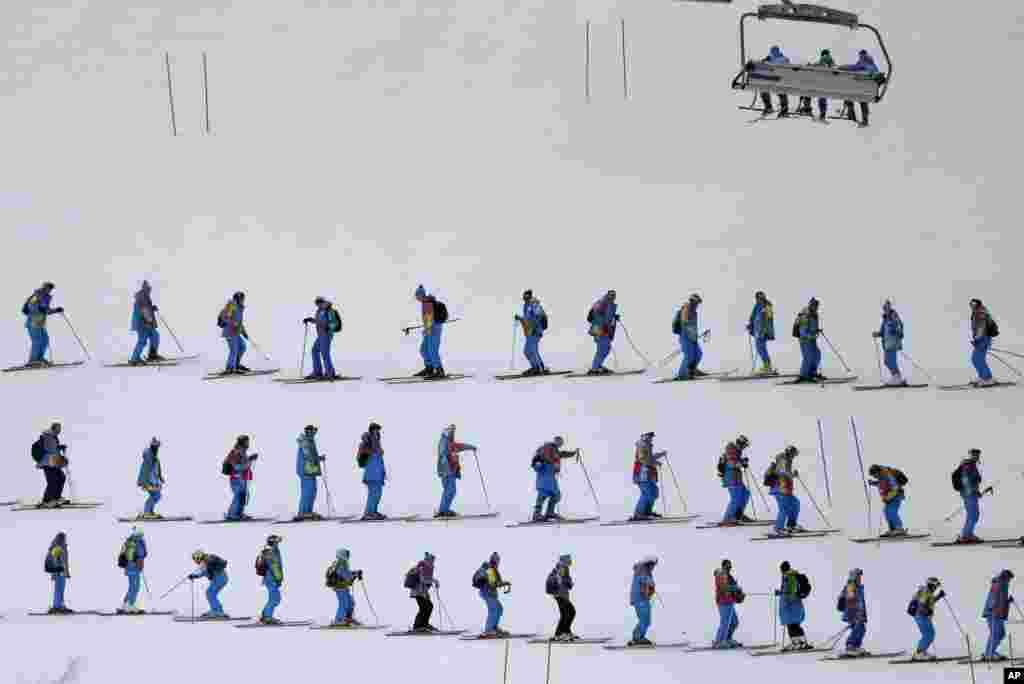 14일 여성 활강스키 경기에 앞서 인부들이 스키장 경사면을 고르고 있다.