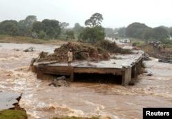 A man looks at a washed away bridge along Umvumvu river following Cyclone Idai in Chimanimani, Zimbabwe, March 18, 2019.