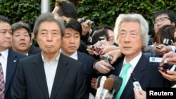 Former Japanese prime ministers Junichiro Koizumi (front R) and Morihiro Hosokawa (front L) are surrounded by the media after their meeting in Tokyo, Jan. 14, 2014.