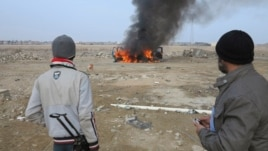 Sunni Muslim fighters watch as a police vehicle burns during clashes in Ramadi, Jan. 2, 2014.